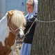 An Amish girl waits in line to auction off her pony at the large-animal stable.