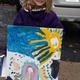 Grace Kennedy, 6, poses with the GOOD sign that 'splattered' her and her family.