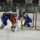 Junior forward Mark Gorman (19) digs for the puck in front of the Methuen net.
