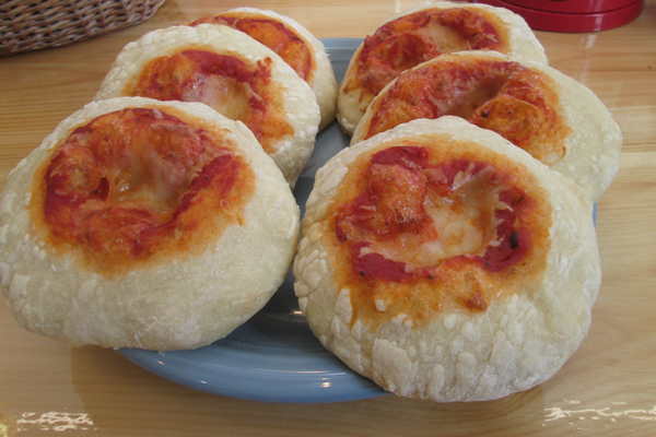 Small pizzas on fresh rolls are served to go.