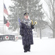 "A snow-covered bugler stands at attention after sounding ""Taps"" for Richard Pinter, who was known as The Lone Bugler."