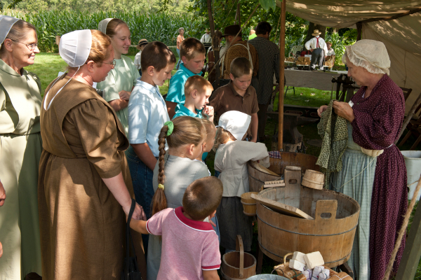Watsontown resident Eileen Anderson explains how clothes were made clean in the 1850s to an attentive group of visitors.  They take turns rubbing handmade soap into clothes using the washing stick, and are fascinated when she drops a sizzling cannonball in the tub to reheat the water!   Photo by Jim Walter.