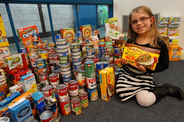 Dewing Elementary School student Abigail Downing shows one of the packages she contributed to the total of 606 items donated to the Tewksbury Community Pantry.