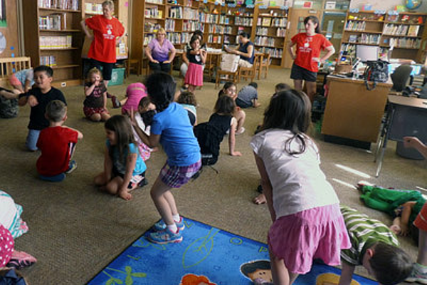 Carolyn Carey (L-red shirt, standing) and Anne Carey (R- red shirt standing) lead the kindergarteners of Macy in some drama and movement