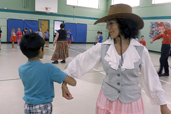 Teacher Maria Eydenberb dances with 2nd grader Eshaan Potnis