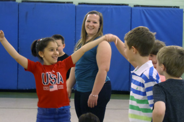 (L-R): Second grader Aris Pavel and Braedon Murphy (striped shirt) dance while teacher Nikole Auger waits her turn