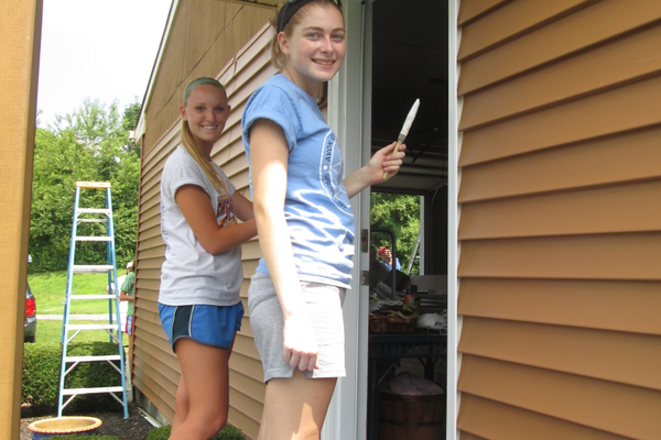 Two teens paint the door frame of a home in Kennett Square on Monday afternoon.