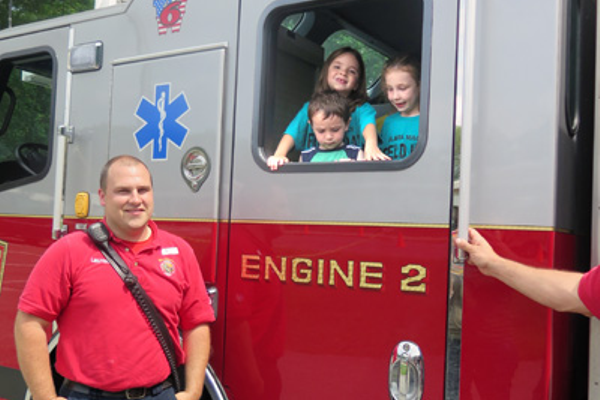 Lt. Bangma of the Bellingham Fire Dept. assists Macy students during touch-a-truck event.