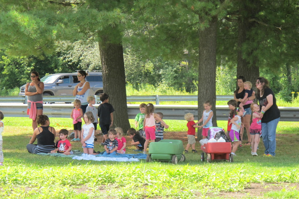 A preschool group catches some shade while enjoying the Summer Concert