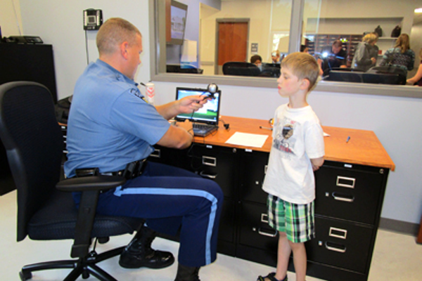 Massachusetts State Trooper Matthew Guarino takes a photo of Bellingham's Aidan Doyle for his child ID kit.
