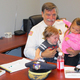 Police Chief Gerry Daigle sits at his desk in his new office with his grandson Camden Polo and granddaughter Aaliyah Daigle.