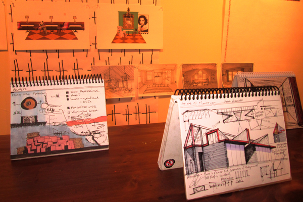 Sketchbooks belonging to three local architects are displayed on tables, with enlargements of some of their pages behind them.