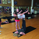 Students Annie Bunker and Bayley Johnson concentrate while moving into 'Full Bow.' This is one of the fundamental poses in beginner AcryoYoga.