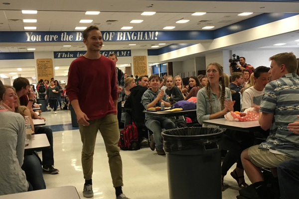 Dallin Bentley walks up to the front of the Bingham High School lunchroom to accept a $20,000 scholarship from Footlocker. – Tori La Rue