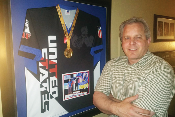 Draper's Robert Baxter poses next to his jersey and the gold medal he won as the world arm wrestling champion in the unlimited masters division. —Ron Bevan