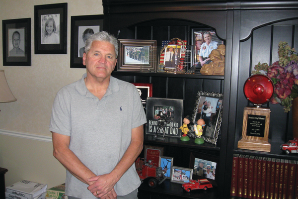 Tom Roberson, a retired firefighter and former medic, stands before his shelves of awards and pictures from his time as a firefighter. Roberson, Ron Voorhees, Barry Olsen and Andrew Hutchison all combined to save Jim Knutson's life after he collapsed into cardiac arrest during church on Sunday, May 22. —Travis Barton