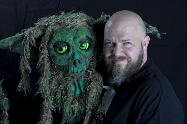 "Russ Adams smiles next to one of his creature creations. Adams' work has been seen in multiple movies and is possibly best known for his appearance as a contestant on the SyFy television show, ""Jim Henson's Creature Shop Challenge."" – Escape Design FX"