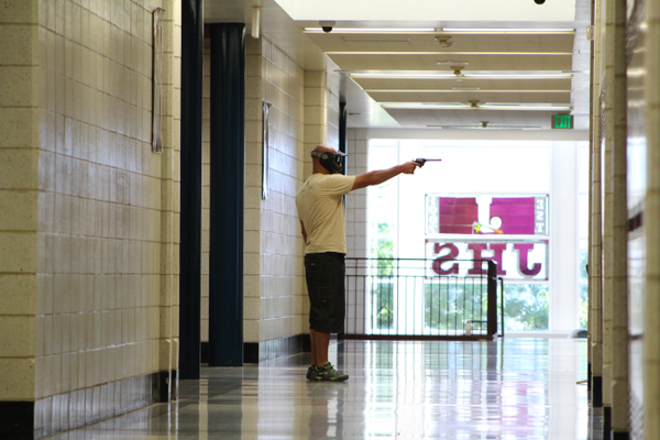 Utah Highway Patrol Sgt. Daniel Krum fires blanks from a revolver to start an active shooter drill at Jordan High School on July 5, 2016. (Photo: Chris Larson, Sandy City Journal)