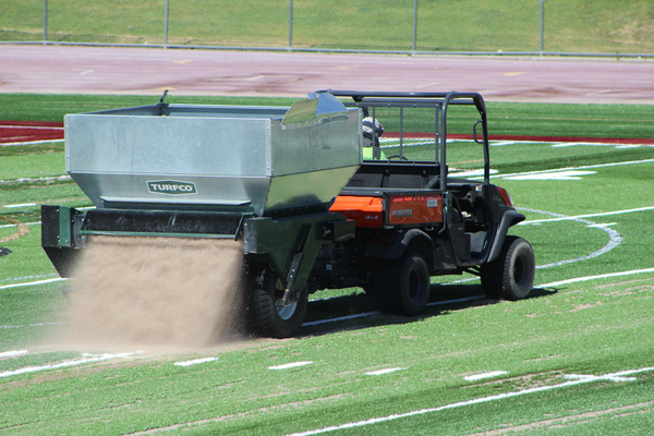 FieldTurf employee Cole dumps sand onto the turf for fill. The sand appeared to be swallowed into the turf as it settled to the base layer of fill. (Photo: Chris Larson, Sandy City Journal)