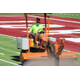 "Kyle Falslev, FieldTurf superintendent and installer, runs the ""spreader"" over the south portion of the Jordan High School turn field, throwing up cryogenically frozen then crushed rubber crumbs which act as fill for the turf. (Photo: Chris Larson, Sandy City Journal)"