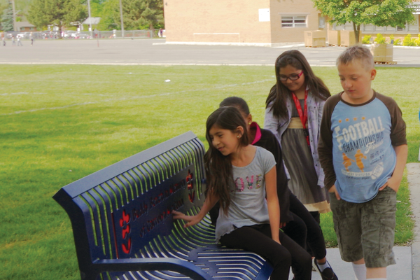 Midvalley Students in Carrolyn McCann's third-grade class exam the new bench memorializing their teacher who died earlier in the school year. — Julie Slama
