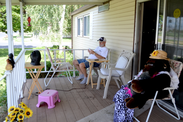 Larry Milligan sits outside his Winchester Estates home. The property on which these mobile homes reside has been put up for sale. –Kimberly Roach