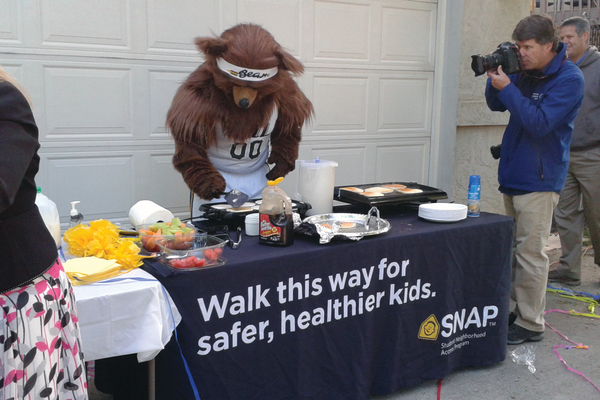 The Christiansen family, friends and neighbors watch the Utah Jazz Bear flips pancakes on May 10, who then joined them to walk to Altara Elementary. The family won the Utah Department of Transportation's Spring Walk 'n Win contest, which gave the school $500. — Wendy Christiansen