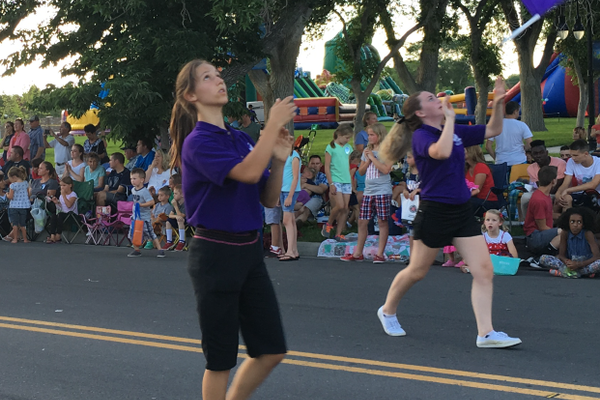 Riverton High School color guard members twirl flags at the Riverton City Town Days parade. –Tori La Rue