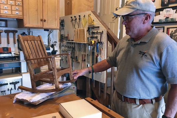 Bart Kadleck looks over the child-sized rocking chair he's building for a client overseas. Bart began woodworking out of the garage in his Taylorsville townhome after his diagnosis of Parkinson's Disease kept him from pursuing his career as a pilot. – Tori La Rue