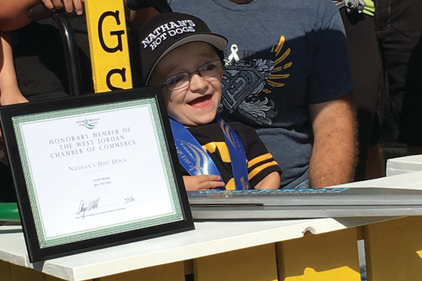 "9-year-old Nathan Glad shouts ""Hooray"" after cutting the ceremonial ribbon at the grand opening of his hot dog stand. –Tori La Rue"