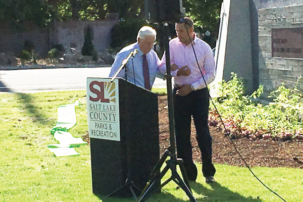 Chris Swensen (right) helps his father Gary Swensen to the pulpit during the renaming ceremony for Gary C. Swensen Valley Regional Park. In the past, Gary worked as Salt Lake County's land acquisitioner and superintendent and director of parks and recreation, so community members voted to name the county's park in Taylorsville after him. –Tori La Rue
