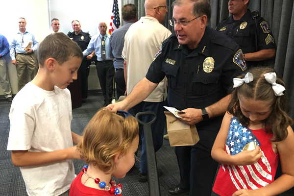 West Jordan Police Chief Doug Diamond hands out sticker badges to the children who gave his officers gift packages. –Tori La Rue