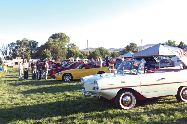 Spectators look around at vintage and muscle cars during the Old West Days car show in Bluffdale. –Tori La Rue