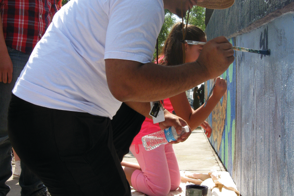 Solo Tuiaki paints his name onto the end of the mural he helped paint with kids from the Salt Lake County Housing Authority. –Travis Barton