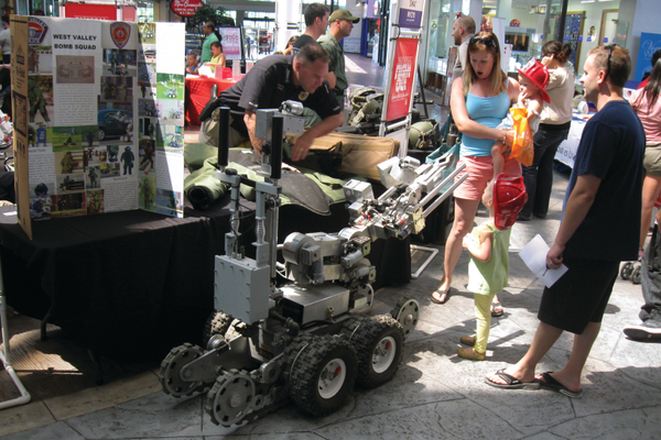 A West Valley family checks out the robot used by the West Valley Bomb Squad at the Police Safety Fair at Valley Fair Mall on Aug. 13. –Travis Barton