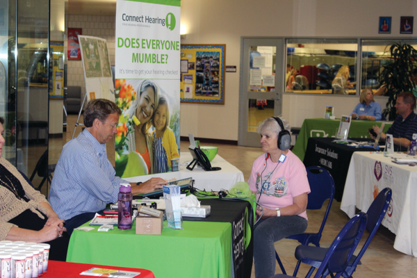 Charles Dunford of Connect Hearing, left, conducts a hearing test on Vickie Banks, right, at the West Valley City Night Out Against Crime Senior Safety & Health Fair on Aug. 15. - Chris Larson