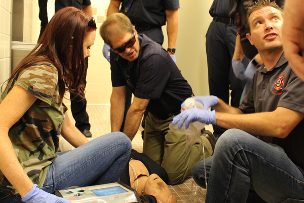 L to R: Councilmembers Kristin Coleman-Nicholl, District 3, Chris McCandless, District 4, and City Council Office Director Mike Applegarth working in a CPR simulation on a dummy acting as analog for a full respiratory arrest victim in the men's room of the south-side of the Sandy City Hall on Aug. 23, 2016. (My City Journals/Chris Larson)