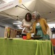 Cynde Howells (left) and Barbara Pioli look at some of the raffle prizes after Howells won a raffle prize. She donated her prize to the next person to sign up for the Wasatch Cooperative Market. (Travis Barton/City Journals)