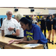 Ginger Lei Wright converses with scorekeepers before the Taylorsville High School and Jordan High School varsity volleyball game on Sept. 13. Ginger Lei, a senior, continues to attend every game after an injury kept her from playing at the start of the season. (Tori La Rue/City Journals)