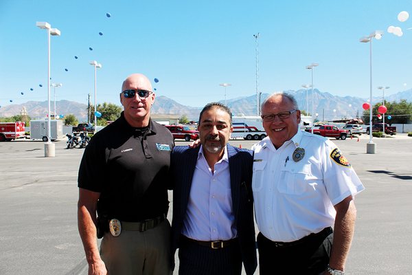 South Salt Lake Police Chief Jack Carruth and Fire Chief Ron Morris with their host (Orlando Rodriguez/City Journals)