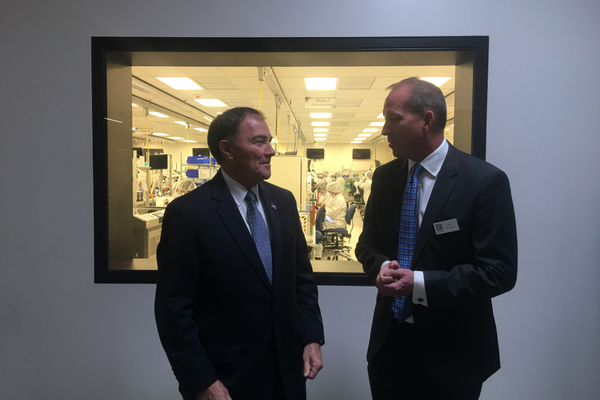 Gov. Gary Herbert and Ken Eliason of Edward Life Sciences discuss the medical devices produced at the plant in Draper. (Kelly Cannon/City Journals)