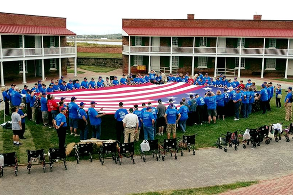 Utah Veterans stand out of their wheelchairs and hold the edges of an American flag at a ceremony at Fort McHenry in Baltimore as part of an Honor Flight. Max Freestone, a Taylorsville resident, was part of the group trip to Washington, D.C. and the surrounding area. (Melanie Sparr/Utah Air National Guard, Honor Flight)