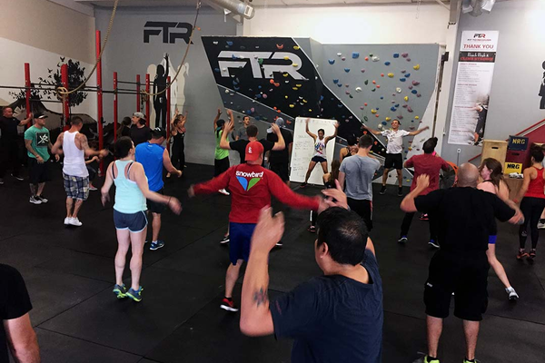 Attendees of the Saturday morning bootcamp finish a set of jumping jacks at the FTR gym. Loud, upbeat music and enthusiastic leadership help FTR stand out as a high-energy, supportive community where everyone is working toward a collective goal of living a life of sobriety. (City Journals)