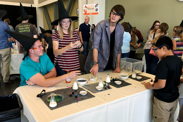 "Members of the Westminster College chapter of the American Chemical Society help a child create a ""potion"" during the Viridian Event Center's Roald Dahl Day celebration on Oct. 7. (Tori La Rue/City Journals)"
