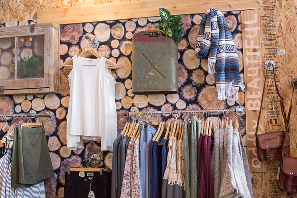 A clothing display with natural wood stumps as a backdrop at Unhinged.