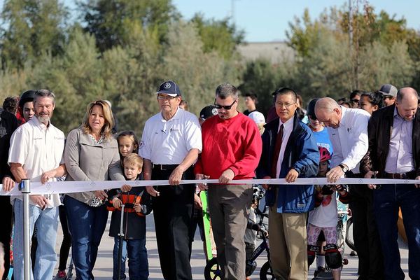 Members of the West Valley City Council prepare to cut the ribbon while Mayor Ron Bigelow helps a child to cut it. More than 40 people participated in the ceremonial ribbon cutting. (Kevin Conde/West Valley City)