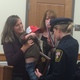 Dracut Police Det. Megan Pike receives a medal from the Middeness family.