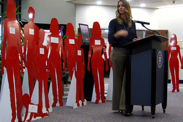 Rachelle Hill speaks in front of a few silent witnesses at city hall on Oct. 25. The 52 red silhouettes were each given names to represent those in the community affected by domestic violence. (Travis Barton/City Journals)