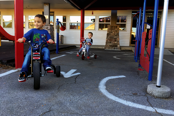 Jayden Kern and Carson Burnett ride tricycles in the biking area of the outdoor classrrom at ABC Beginnings-Redwood. (Travis Barton/City Journals)