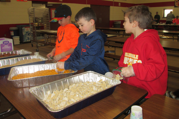 Children carefully scooped snacks into bags at Hillendale.